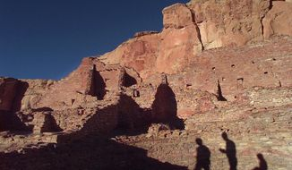 FILE - In this Nov. 21, 1996, file photo, tourists cast their shadows on the ancient Anasazi ruins of Chaco Canyon in N.M. Dozens of protests have been filed by tribal officials, environmentalists and others as federal land managers consider leasing parcels in northwestern New Mexico for oil and gas development that critics say are too close to sites they consider culturally significant. (AP Photo/Eric Draper, File)