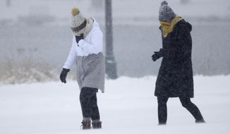 Pedestrians struggle to move as high winds and light snow envelop the pair as they walk in Washington Park as a winter storm sweeps over Colorado's eastern plains and leaves up to a foot of snow in its wake Sunday, Jan. 21, 2018, in Denver. Forecasters predict that the fast-moving storm will move out of the region by late afternoon and into the upper Midwest, creating potential problems for Monday-morning commuters. (AP Photo/David Zalubowski)