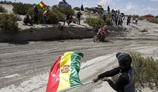 In this Saturday, Jan. 13, 2018 photo, spectators wave Bolivian flags as France's Gasgas motorbike rider Johnny Aubert races during stage 7 of the Dakar Rally between La Paz and Uyuni, Bolivia. (AP Photo/Ricardo Mazalan)