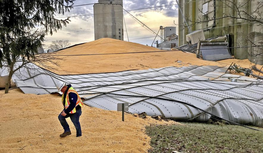 An AT&T worker walks through thousands of bushels of corn that cover Ohio Route 571 Monday, Jan. 22, 2018, after a grain bin at Miami Valley Feed and Grain collapsed on Sunday evening in New Carlisle, Ohio. Emergency personnel were still assessing the scene Monday morning. (Bill Lackey/Dayton Daily News via AP)