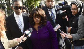 FILE - In a Dec, 4, 2017 file photo, former congresswoman Corrine Brown walks into Federal Court accompanied by pastor Rudolph McKissick, Sr. Brown appeared in Federal Court to be sentenced on fraud charges. Former Florida congresswoman Brown is asking a federal judge to extend by 30 days the date she must report to prison for her fraud conviction. Brown's attorneys filed the request Monday, Jan. 22, 2018, in federal court in Jacksonville, Fla. (Bob Mack/The Florida Times-Union via AP)
