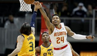 Atlanta Hawks' Kent Bazemore, right, reaches for the ball against Utah Jazz's Ricky Rubio, of Spain, in the first quarter of an NBA basketball game in Atlanta, Monday, Jan. 22, 2018. (AP Photo/David Goldman)
