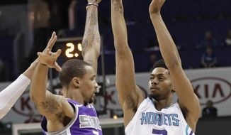 Charlotte Hornets' Jeremy Lamb, right, shoots over Sacramento Kings' George Hill, left, during the first half of an NBA basketball game in Charlotte, N.C., Monday, Jan. 22, 2018. (AP Photo/Chuck Burton)