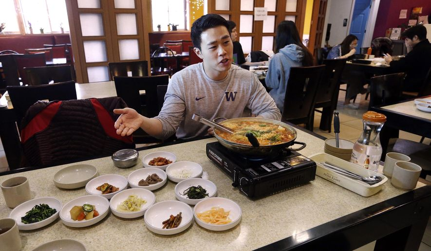 "In this photo taken Dec. 12, 2017, server Young Kim talks about the South Korean dish called budae jjigae, or ""army stew,"" he is serving simmering atop a heating plate at a Korean restaurant in Shoreline, Wash. SPAM, trout, fried chicken, moon pies and anything slathered in mayonnaise, those are some of the flavors of South Korea's home cooking that might seem just a bit familiar to the U.S. athletes and hordes of westerners preparing to descend upon the small Asian country for the 2018 Olympic Winter Games. (AP Photo/Elaine Thompson)"