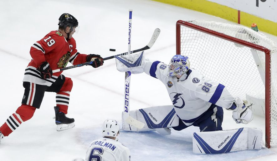 Tampa Bay Lightning goaltender Andrei Vasilevskiy (88) deflects a shot on goal past Chicago Blackhawks' Jonathan Toews (19) during the second period of an NHL hockey game Monday, Jan. 22, 2018, in Chicago. (AP Photo/Charles Rex Arbogast)