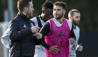 Seattle Sounders midfielder Nicolas Lodiero, front right, jogs around the pitch with Damian Roden, the Sounders' new director of high performance, at the first day of MLS soccer training camp in Tukwila, Wash., Monday, Jan. 22, 2018. (Bettina Hansen/The Seattle Times via AP)