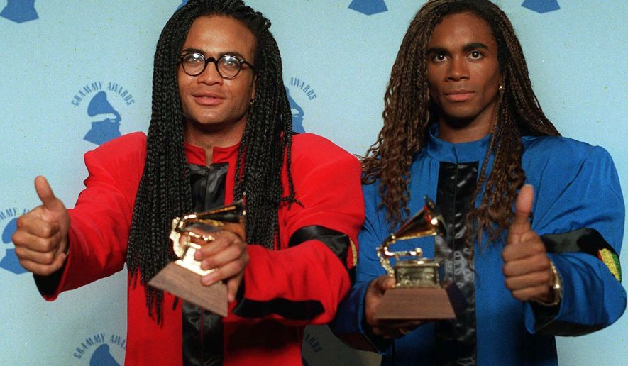 """FILE - In this Feb. 21, 1990 file photo, Rob Pilatus, left, and Fab Morvan of Milli Vanilli give the thumbs-up as they display their Grammys after being presented with the best new artist award in Los Angeles. The Grammys asked the duo to return the award after it was learned that Morvan and Pilatus didn't sing on the duo's 1989 U.S. debut, """"Girl You Know It's True.""""  (AP Photo/Douglas C. Pizac, file)"""