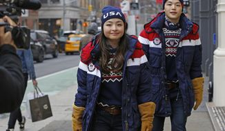 Ice dancing pair and sister and brother Maia and Alex Shibutani, who will participate in the upcoming winter Olympics in Pyeongchang, South Korea, model Team USA's opening ceremony uniforms for a cameraman on the street outside Polo Ralph Lauren's Prince Street store, Monday, Jan. 22, 2018, in New York. (AP Photo/Kathy Willens)