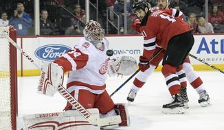 Detroit Red Wings goaltender Petr Mrazek (34) deflects the puck as New Jersey Devils center Brian Boyle (11) looks on during the second period of an NHL hockey game Monday, Jan. 22, 2018, in Newark, N.J. (AP Photo/Bill Kostroun)