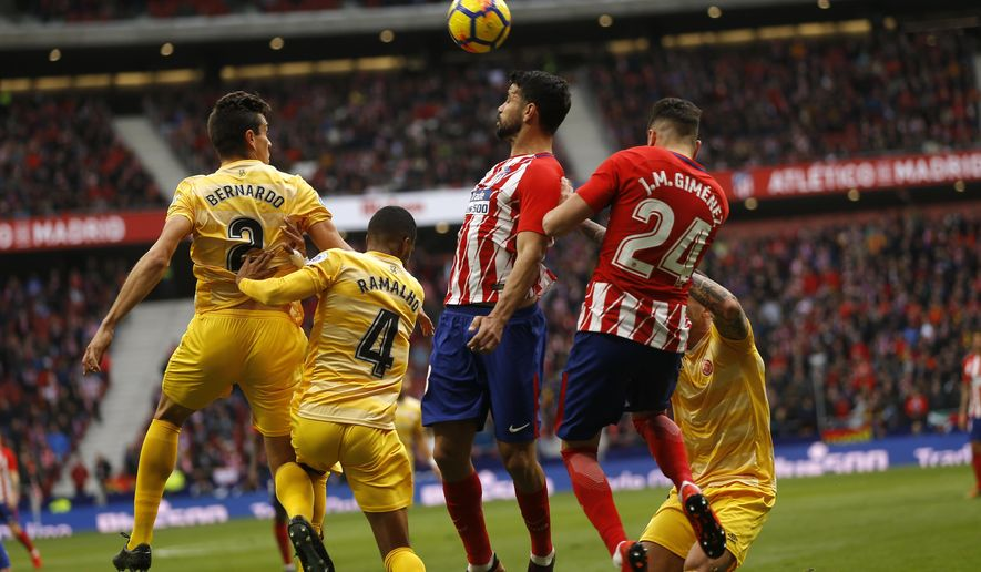 Atletico Madrid's Diego Costa, second right, goes for a header with teammate Jose Maria Gimenez, right, and Girona's Bernardo Espinosa, left, and Jonas Ramalho during a Spanish La Liga soccer match between Atletico Madrid and Girona at the Wanda Metropolitano stadium in Madrid, Saturday, Jan. 20, 2018. (AP Photo/Francisco Seco)