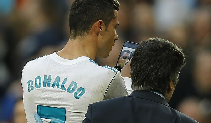 Real Madrid's Cristiano Ronaldo leaves the pitch as he uses a phone to look at himself while bleeding from his forehead during a Spanish La Liga soccer match between Real Madrid and Deportivo Coruna at the Santiago Bernabeu stadium in Madrid, Sunday, Jan. 21, 2018. Ronaldo scored twice in Real Madrid's 7-1 victory. (AP Photo/Francisco Seco)