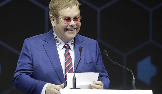 British musician Elton John delivers a speech during the ceremony for the Crystal Awards on the eve of annual meeting of the World Economic Forum in Davos, Switzerland, Monday, Jan. 22, 2018. The award celebrates the achievements of leading artists who are bridge-builders and role models for all leaders of society. (AP Photo/Markus Schreiber)