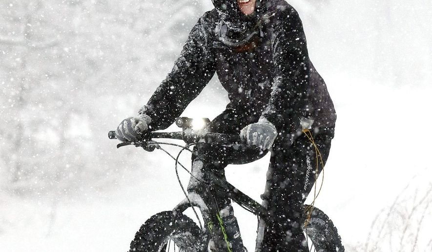 Janis Ray of Eau Claire, Wis. rides her fat tire bike Monday, Jan. 22, 2018, down a city trail during the season's biggest winter storm to hit the region. Most area schools were closed and travel was hazardous throughout western Wisconsin. (Steve Kinderman/The Eau Claire Leader-Telegram via AP)