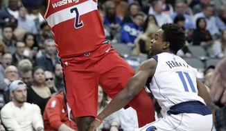 Washington Wizards guard John Wall (2) is fouled taking a shot by Dallas Mavericks' Yogi Ferrell (11) in the first half of an NBA basketball game, Monday, Jan. 22, 2018, in Dallas. (AP Photo/Tony Gutierrez)