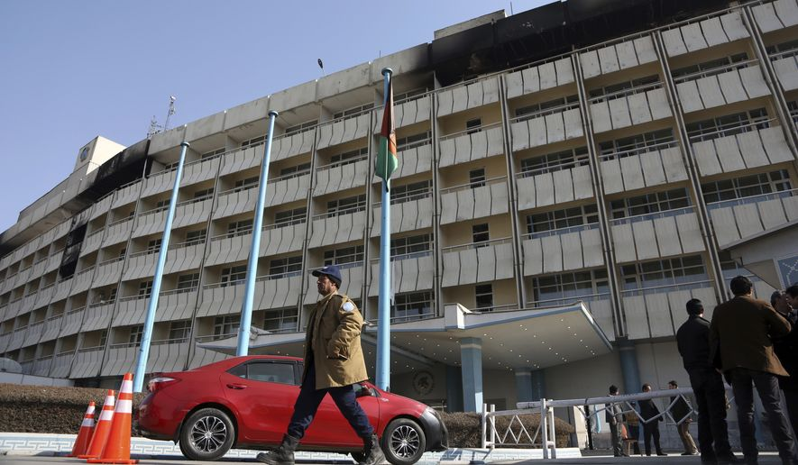 An Afghan security stand guard walks in front of the Intercontinental Hotel in Kabul, Afghanistan, Tuesday, Jan. 23, 2018. Survivors of the Taliban attack on Kabul's Intercontinental Hotel gave harrowing accounts on Monday of the 13-hour weekend standoff. The siege ended on Sunday with Afghan security forces saying they had killed the last of six Taliban militants who stormed the hotel in suicide vests late the previous night, looking for foreigners and Afghan officials to kill. (AP Photo/Rahmat Gul)