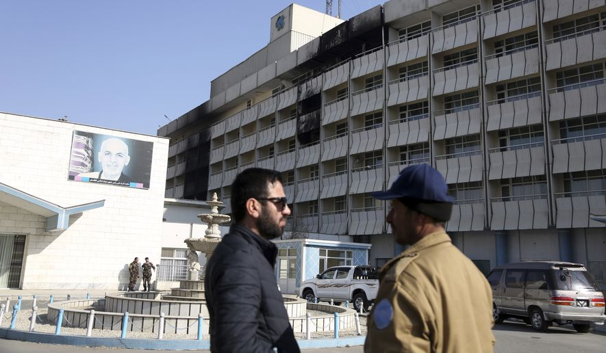 An Afghan security guard, right, stands in front of the Intercontinental Hotel after a deadly attack in Kabul, Afghanistan, Tuesday, Jan. 23, 2018. Survivors of the Taliban attack on Kabul's Intercontinental Hotel gave harrowing accounts on Monday of the 13-hour weekend standoff. The siege ended on Sunday with Afghan security forces saying they had killed the last of six Taliban militants who stormed the hotel in suicide vests late the previous night, looking for foreigners and Afghan officials to kill. (AP Photo/Rahmat Gul)