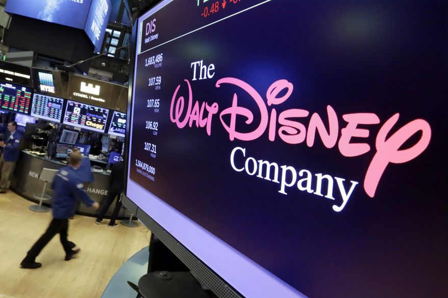 FILE - In this Monday, Aug. 7, 2017, file photo, The Walt Disney Co. logo appears on a screen above the floor of the New York Stock Exchange. The Walt Disney Co. announced Tuesday, Jan. 23, 2018, that it will give more than 125,000 eligible employees a one-time $1,000 cash bonus and invest $50 million in an education funding program. (AP Photo/Richard Drew, File)