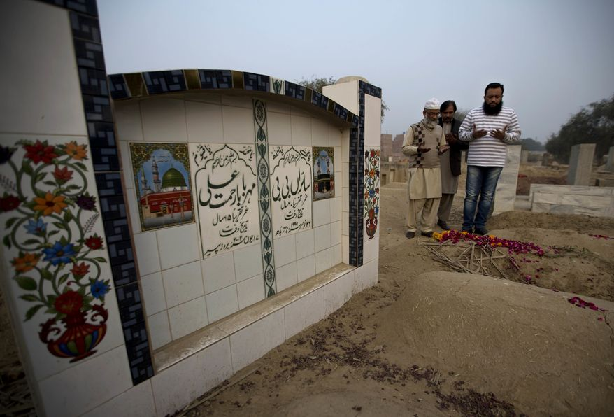 In this Thursday, Jan. 18, 2018 photo Mohammed Amin, left, offer prayers at a grave of his seven year-old daughter Zainab Ansari in Kasur, Pakistan. The brutal rape of Zainab, whose body was left in a garbage dump earlier this month, has roiled Conservative Pakistan and revealed a sexual predator who has raped and killed at least 11 girls in Zainab's hometown of Kasur. (AP Photo/B.K. Bangash)