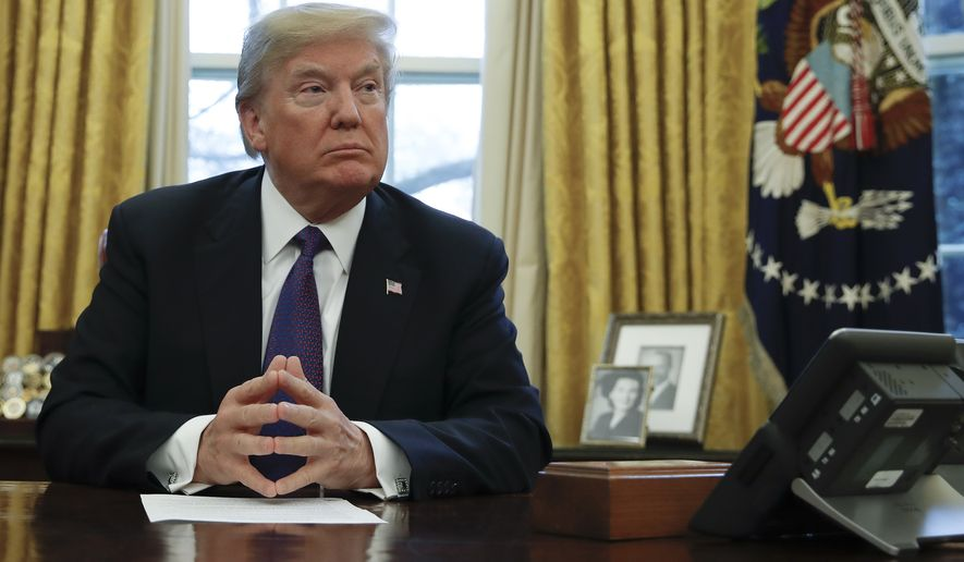 "President Donald Trump prepares to sign Section 201actions in the Oval Office of the White House in Washington, Tuesday, Jan. 23, 2018. Trump says he is imposing new tariffs to ""protect American jobs and American workers."" Trump acted to impose new tariffs on imported solar-energy components and large washing machines in a bid to help U.S. manufacturers. (AP Photo/Carolyn Kaster)"