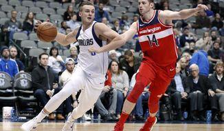 Dallas Mavericks guard Kyle Collinsworth drives to the basket as Washington Wizards forward Jason Smith (14) defends during an NBA basketball game, Monday, Jan. 22, 2018, in Dallas. (AP Photo/Tony Gutierrez)