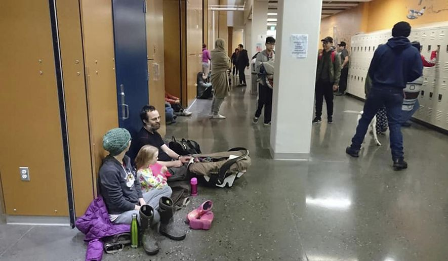 Evacuees gather at Kodiak High School in Kodiak, Alaska, Tuesday, Jan 23, 2018, after an earthquake and tsunami alert. A powerful undersea earthquake sent Alaskans fumbling for suitcases and racing to evacuation centers in the middle of the night Tuesday after a cellphone alert warned that a tsunami could smash into the state's southern coast and western Canada. (Grigore Ciubotaru via AP)