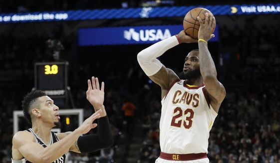 Cleveland Cavaliers forward LeBron James (23) shoots and scores over San Antonio Spurs guard Danny Green (14) during the first half of an NBA basketball game, Tuesday, Jan. 23, 2018, in San Antonio. The score allowed James to reach the 30,000 milestone for his career. (AP Photo/Eric Gay)