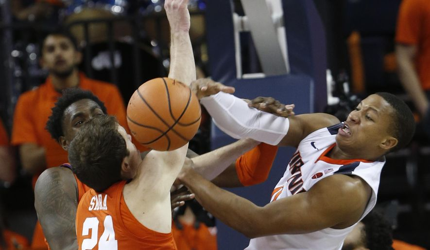 Virginia guard Devon Hall, right, competes for a rebound with Clemson forwards David Skara (24) and Elijah Thomas, left rear, during the first half of an NCAA college basketball game in Charlottesville, Va., Tuesday, Jan. 23, 2018. (AP Photo/Steve Helber) ** FILE **
