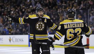 Boston Bruins center Patrice Bergeron (37) celebrates his goal with left wing Brad Marchand (63) during the second period of an NHL hockey game against the New Jersey Devils on Tuesday, Jan. 23, 2018, in Boston. (AP Photo/Charles Krupa)