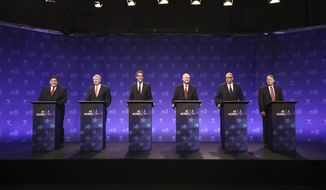 Democrats running for Illinois governor, from left, billionaire J.B. Pritzker, businessman Chris Kennedy, and state Sen. Daniel Biss, educator Robert Daiber, activist Tio Hardiman, and physician Robert Marshall take their podium positions before a televised forum Tuesday, Jan. 23, 2018, in Chicago. The six Democrats are vying for the chance to unseat Republican Gov. Bruce Rauner on March 20. (John J. Kim/Chicago Tribune via AP, Pool)