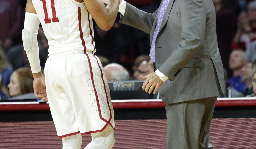 Oklahoma head coach Lon Kruger high-fives Trae Young (11) during the first half of an NCAA college basketball game in Norman, Okla., Tuesday, Jan. 23, 2018. (AP Photo/Garett Fisbeck)
