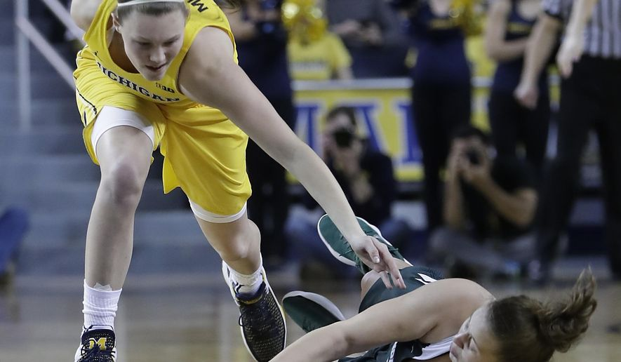 Michigan guard Nicole Munger, left, and Michigan State center Jenna Allen (33) chase the loose ball during the first half of an NCAA college basketball game, Tuesday, Jan. 23,2018, in Ann Arbor, Mich. (AP Photo/Carlos Osorio)