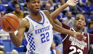 Kentucky's Shai Gilgeous-Alexander (22) passes while defended by Mississippi State's Tyson Carter (23) during the first half of an NCAA college basketball game, Tuesday, Jan. 23, 2018, in Lexington, Ky. (AP Photo/James Crisp)