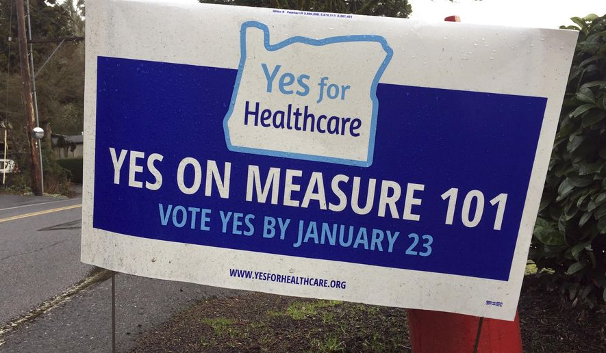 FILE - In this Jan. 19, 2018, file photo. a sign in support of Oregon's Measure 101 is displayed by a homeowner along a roadside in Lake Oswego, Ore. The taxes before voters in the special election on Tuesday, Jan. 23, 2018, are a short-term fix for health care funding designed to generate between $210 and $320 million in revenue over two years. Oregon aggressively expanded its Medicaid rolls under the Affordable Care Act and now, just 5 percent of its population is uninsured. But state lawmakers have struggled to come with a long-term funding plan. (AP Photo/Gillian Flaccus, File)