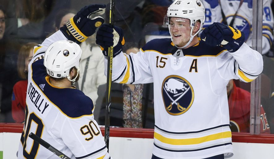 Buffalo Sabres' Jack Eichel, right, celebrates his game-winning goal during overtime period NHL hockey action against the Calgary Flames in Calgary, Alberta Monday, Jan. 22, 2018. (Jeff McIntosh/The Canadian Press via AP)