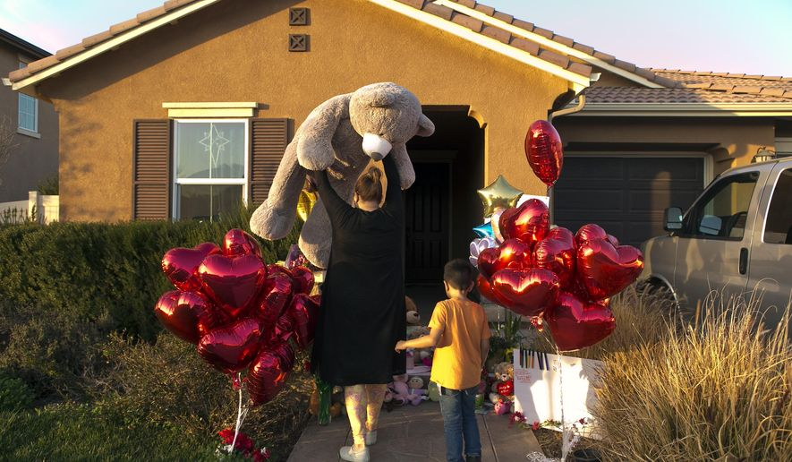 "FILE--In this Jan. 18, 2018, file photo, neighbor Liza Tozier, and her son, Avery Sanchez, 6, drop off his large ""Teddy"" as a gift for the children who lived on a home where police arrested a couple accused of holding 13 children captive in Perris, Calif., More than $120,000 has been donated to help the 13 siblings who authorities say were kept chained to beds for months by their parents and starved so much that their growth was stunted. (AP Photo/Damian Dovarganes, file)"