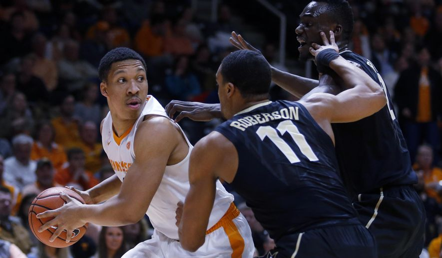 Tennessee forward Grant Williams (2) is defended by Vanderbilt forward Jeff Roberson (11) and Vanderbilt center Djery Baptiste, right, in the first half of an NCAA college basketball game Tuesday, Jan. 23, 2018, in Knoxville, Tenn. (AP Photo/Crystal LoGiudice)