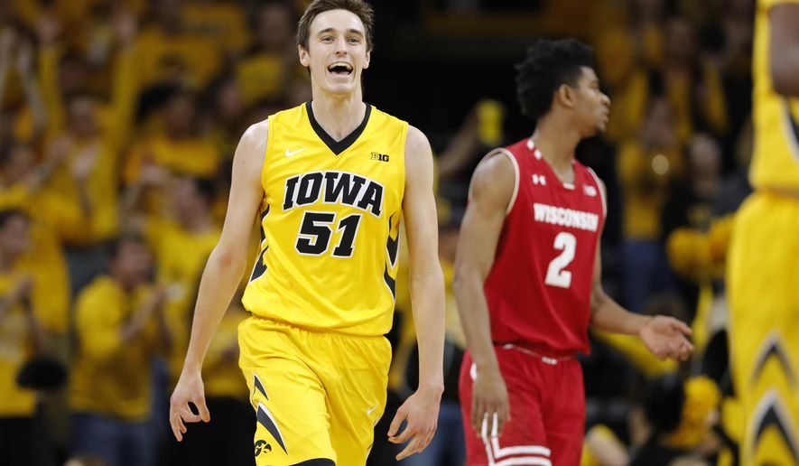 Iowa forward Nicholas Baer (51) celebrates in front of Wisconsin forward Aleem Ford (2) after making a 3-point basket during the first half of an NCAA college basketball game Tuesday, Jan. 23, 2018, in Iowa City, Iowa. (AP Photo/Charlie Neibergall)