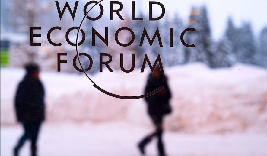 Guests bound for the World Economic Forum in Davos, Switzerland, navigate a snowy walkway. Many arrived, however, in a private jet. (Associated Press)