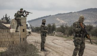 Turkey-backed Free Syrian Army fighters secure an area where Turkish army's Operation Olive Branch continue in Azaz, Syria on Wednesday.  Turkish officials have talked about expanding the Syrian incursion to target Manbiji, held by U.S.-allied Kurds. (ASSOCIATED PRESS PHOTOGRAPHS)
