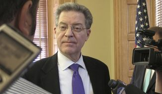 Kansas Gov. Sam Brownback answers questions from reporters after legislative leaders give the final go-ahead to a plan to build a new state prison, Wednesday, Jan. 24, 2018, at the Statehouse in Topeka, Kan. The state plans to have the nation's largest private-prison operator build the new facility and lease it to the state for its first 20 years in operation. (AP Photo/John Hanna)