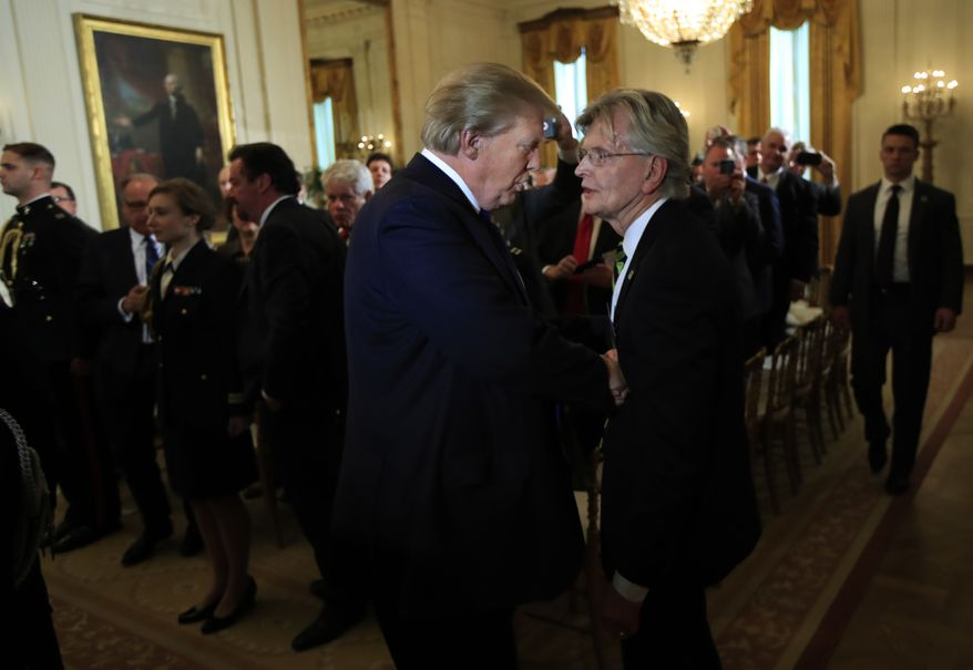 President Donald Trump, shakes hands with Hope Township, N.J. Mayor Timothy McDonough, right, as he leaves a gathering of mayors in the East Room of the White House in Washington, Wednesday, Jan. 24, 2018. (AP Photo/Manuel Balce Ceneta)