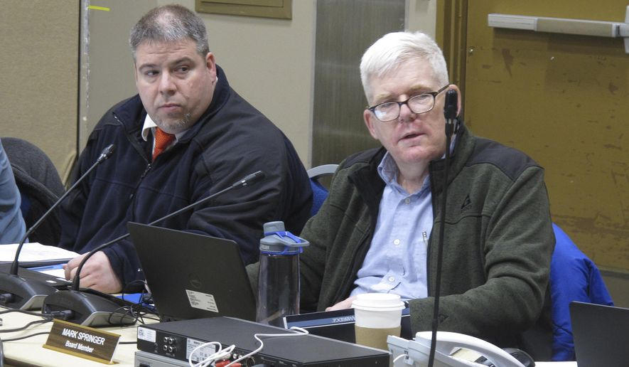 Travis Welch, left, and Mark Springer are sit during a meeting of the Alaska Marijuana Control Board on Wednesday, Jan. 24, 2018, in Juneau, Alaska. Welch was recently chosen by Gov. Bill Walker to fill the board's public safety seat after another member resigned. Springer was elected as board chairman on Wednesday. (AP Photo/Becky Bohrer)