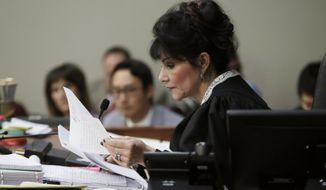 """Judge Rosemarie Aquilina reads excerpts from the letter written by Larry Nassar during the seventh day of Nassar's sentencing hearing Wednesday, Jan. 24, 2018, in Lansing, Mich.  The former sports doctor who admitted molesting some of the nation's top gymnasts for years was sentenced Wednesday to 40 to 175 years in prison as Aquilina declared: """"I just signed your death warrant.""""  The sentence capped a remarkable seven-day hearing in which scores of Larry Nassar's victims were able to confront him face to face in a Michigan courtroom. (AP Photo/Carlos Osorio)"""