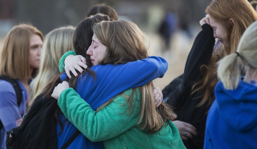 Students embrace following a prayer vigil at Paducah Tilghman High School in Paducah, Ky., Wednesday, Jan. 24, 2018, in Paducah, Ky. The gathering was held for the victims of the Marshall County High School shooting on Tuesday. (Ryan Hermens/The Paducah Sun via AP)
