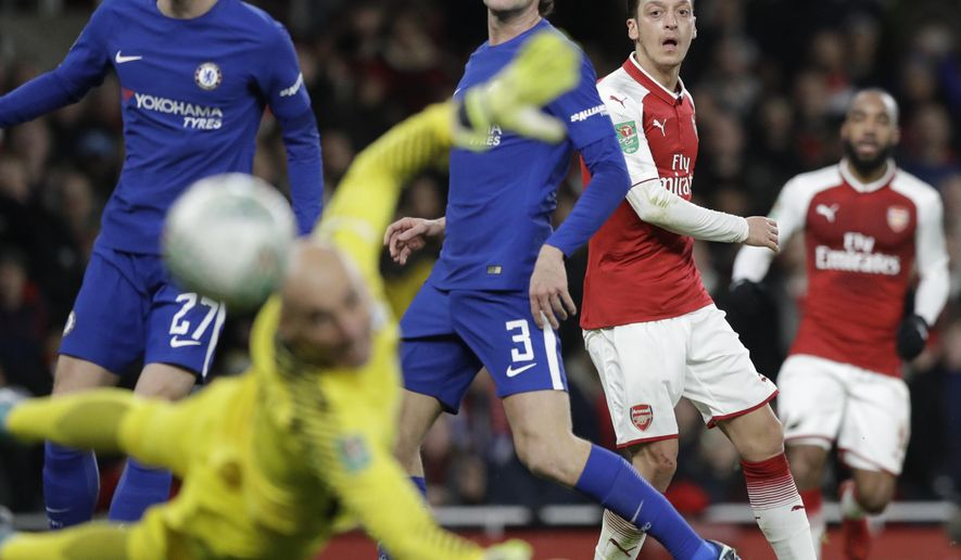 Arsenal's Mesut Ozil, right, shoots during the English League Cup semifinal second leg soccer match between Chelsea and Arsenal at the Emirates stadium in London, Wednesday, Jan.24, 2018. (AP Photo/Matt Dunham)