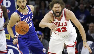Chicago Bulls center Robin Lopez (42) and Philadelphia 76ers guard Ben Simmons (25) chase a rebound during the first half on an NBA basketball game Wednesday, Jan. 24, 2018, in Philadelphia. (AP Photo/Laurence Kesterson)