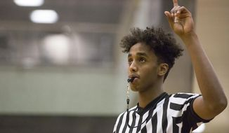 In a Jan. 11, 2018 photo, Pronghorns' Abdul Mohamed holds up one finger to let everyone know there is one foul shot left as he referees the women's intramural basketball game at the Recreation Center in Gillette, Wyo.  (Kelly Wenzel/Gillette News Record via AP)