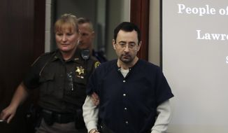 Dr. Larry Nassar is escorted into court during the seventh day of his sentencing hearing Wednesday, Jan. 24, 2018, in Lansing, Mich. Nassar has admitted sexually assaulting athletes when he was employed by Michigan State University and USA Gymnastics, which is the sport's national governing organization and trains Olympians. (AP Photo/Carlos Osorio)