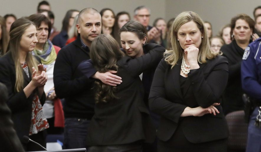 Former gymnast Rachael Denhollander, center, is hugged after giving her victim impact statement during the seventh day of Larry Nassar's sentencing hearing Wednesday, Jan. 24, 2018, in Lansing, Mich. At right is Assistant Attorney General Angela Povilaitis. Nassar has admitted sexually assaulting athletes when he was employed by Michigan State University and USA Gymnastics, which is the sport's national governing organization and trains Olympians. (AP Photo/Carlos Osorio)