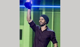 FILE - In this Oct. 26, 2017 file photo, Enrique Iglesias accepts the artist of the year award at the Latin American Music Awards in Los Angeles. Iglesias is suing Universal Music Group in a dispute over how much he is paid for songs played on streaming music services. (Photo by Chris Pizzello/Invision/AP, File)